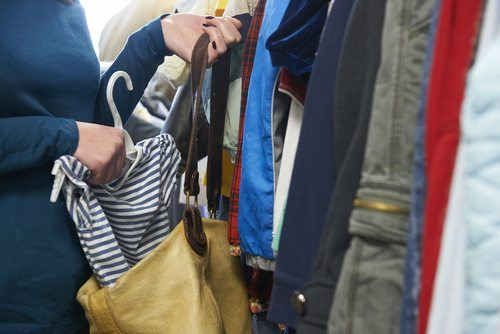 Woman in clothing store placing striped shirt into her purse