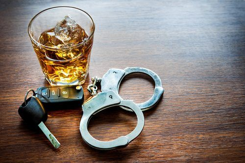 Wooden table with car keys, handcuffs, and what looks to be quite a nice bourbon on the rocks